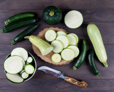 Set of knife and other zucchinis in a bowl and around and sliced zucchinis on a dark wooden background. flat lay.