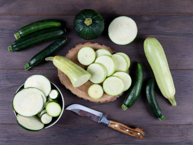 Set of knife and other zucchinis in a bowl and around and sliced