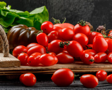 Tomatoes variety in a handmade tray with lettuce side view on wooden and dark background